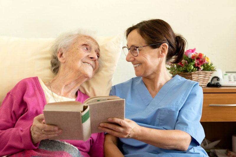 nurse reading a book to an senior patient