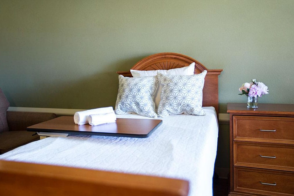 A wooden bed with white pillows