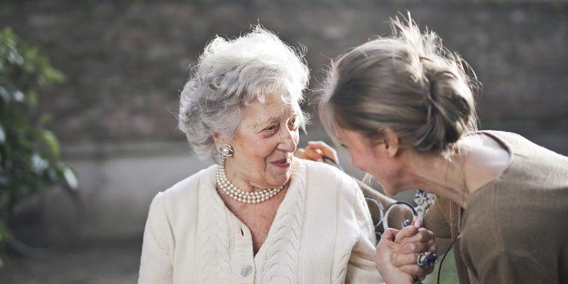 Skilled nurse smiling at elderly patient
