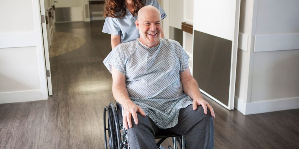 CNA pushing patient in wheelchair after surgery