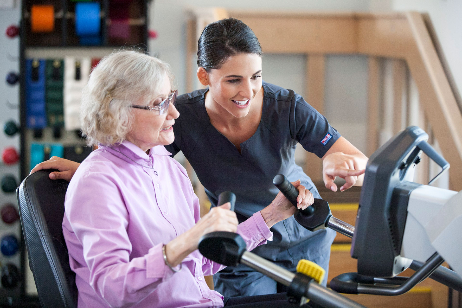 Physical therapist helping woman use equipment