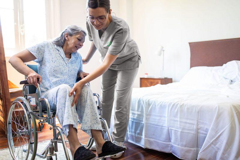 Registered Nurse helping elder woman in bed from their wheelchair