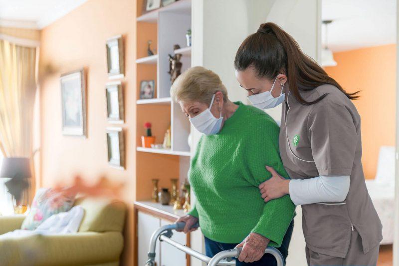 CNA (certified nursing assistant) helping an elderly patient walk with her walker