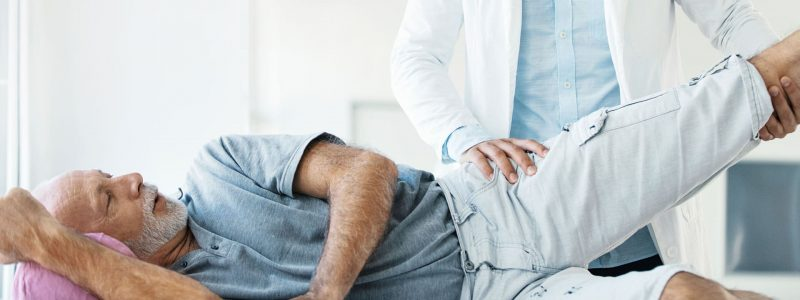 patient getting hip stretch from physical therapist