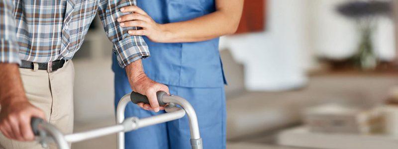 Skilled nurse helping man with walker