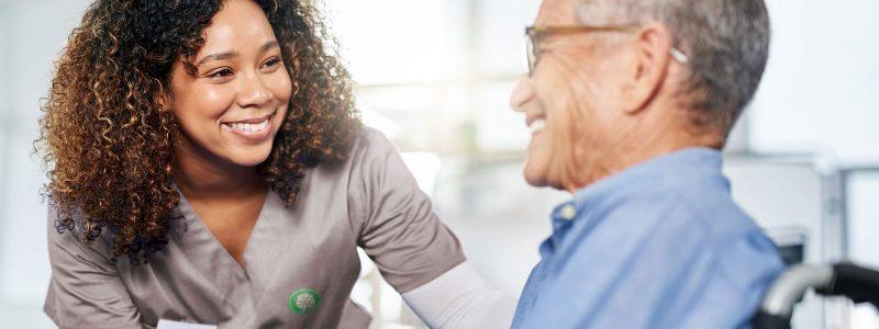 skilled nurse talking with elderly male patient